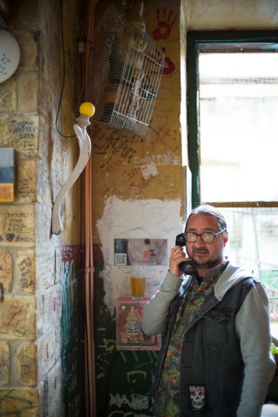 Cserna-Szabó András és a szövegét elmondó telefonkagyló a Szimpla Kertben (fotó: Todoroff Lázár)